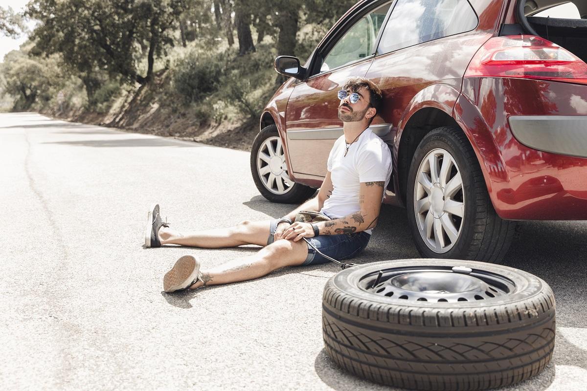 wymiana opony - kierowca siedzi na ziemi oparty o auto