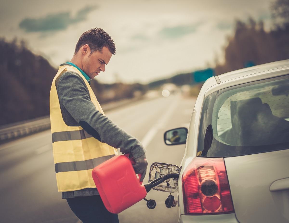mężczyzna dolewa paliwo z karnistra do osobowego auta