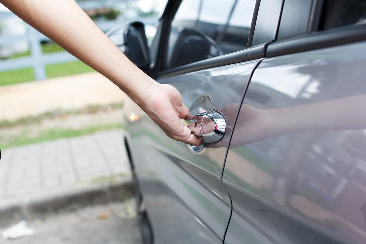 dłoń na klamce od drzwi auta