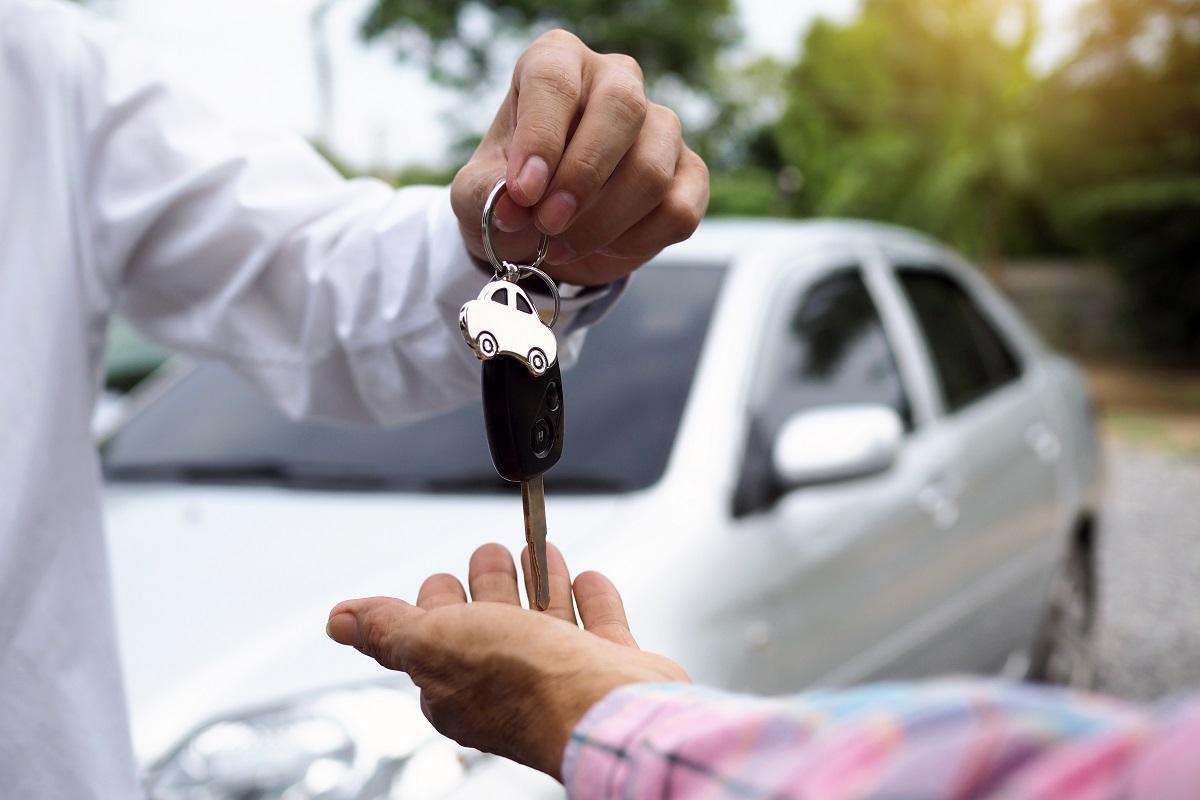 przekazanie kluczyków do samochodu a w tle auto